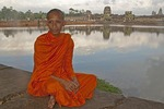 Monk sitting at Angkor Wat west entrance beside moat
