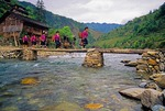 Red Yao nationality women crossing stream in Longsheng County near rice terraces of Longji