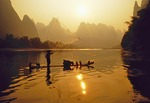 Fisherman on bamboo raft tossing net on Li River near Xingping
