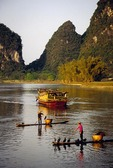 Li River at Yangshuo (near Guilin) with cormorant fishermen on bamboo rafts and family on transport boat