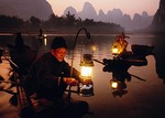 Li River cormorant fishermen on bamboo rafts at dusk  lighting lanterns for night fishing at Xingping (Guilin area)