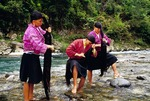 Red Yao minority nationality women combing hair in stream at Huanglo Yao village in Longji (Longsheng County in Guilin area)