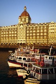 Boats in Mumbai harbour in front of The Taj Mahal Palace Hotel and Tower at Gate of India, built in 1903