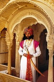 Rajasthani man in traditional dress with sword and jewels standing on ornate balcony of Jaisalmer haveli (mansion) at annual Desert Festival