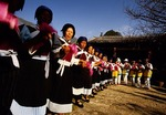 Naxi ethnic minority women  dancing at a monastery during the annual San Duo festival.
