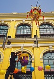 Chinese holiday decorations being hung in Portugese colonial Senado Square