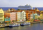 Willemstad's Punda waterfront pastel Dutch architecture with Royal Caribbean cruise ship Adventure of the Seas leaving port