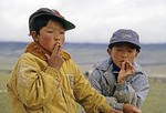 Young Tibetan boys wearing American baseball caps smoking cigarettes