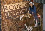 Houston Rodeo tourist posing for photo on a Texas longhorn steer