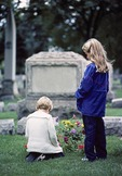 Young children grieving in cemetery