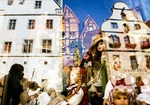 Rothenburg ob der Tauber's medieval old town architecture and a street musician reflected in window of toy shop featuring doll display