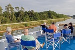Cruise ship passengers on observation deck on Main-Danube Canal watching bicyclists