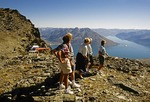 Tourists watch paraglider over Lake Wakatipu's Queenstown Bay from top of Remarkables mountains after helicopter flight