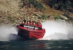 Shotover Jet Boat with tourists on thrill ride on Shotover River near Queenstown