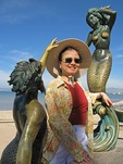 Puerto Vallarta tourist having fun with statues on El Malecon waterfront