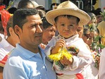 Puerto Vallarta father carrying son in religious procession to the Cathedral of Our Lady of Guadalupe