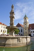 Bratislava's Hlavne Namestie Square with Roland Fountain with statue of Maximilian and Old Town Hall clock tower