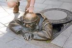 Bratislava tourist getting in touch with public statue of Cumil (The Watcher) in Old Town