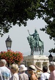 Statue of St Stephen, first Hungarian king, surrounded by tourists on Buda's Castle Hill near Matthias Church in Budapest