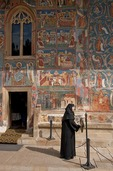 Romanian nun signaling worship service at Voronet Painted Monastery of Bucovina decorated with 15th & 16th century frescoes