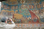 Tourist at Voronet Painted Monastery of Bucovina photographing mural of The Last Judgment