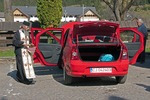 Romanian orthodox priest blessing new Dacia auto with holy water for its owner in Maramures County of northern Transylvania