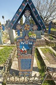 Carved cross marking grave of disabled man in the Merry Cemetery in Sapanta