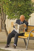 Croatia's Hvar island resident gentleman reading newspaper on bench in Vrisnik