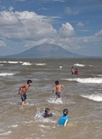 Nicaraguan beach at San Jorge on Lake Nicaragua, kids swimming with Concepcion volcano on Ometepe Island in background