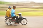 Cambodian (Khmer) couple on motor bike zipping past Angkor Thom