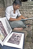 Cambodian artist at Bayon Temple painting Sis stone faces of Boddhisattva at Angkor Thom