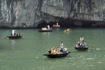 Vietnam tourists boating to explore limestone cave in karst peak on Halong Bay