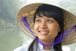 Young Vietnamese woman wearing traditional ao dai dress and conical hat in Hue