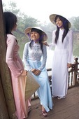 Young Vietnamese women wearing traditional ao dai dresses at Hue's Xung Kheim Pavilion on Luu Kheim Lake in the Royal Mausoleum complex of Nguyen emperor Tu Duc
