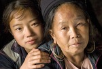 Black Hmong grand daughter with grand mother in village home near Sa Pa in northern hill country of Vietnam