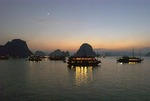 Tourist junks anchored under moon on Halong Bay at night, Vietnam