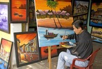 Vietnamese artist Nguyen Tan Hiep painting local scenes in his Hoi An Old Town art gallery