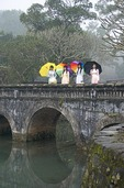 Young Vietnamese women with umbrellas wearing traditional ao dai dresses on stone bridge at Hue's Luu Kheim Lake in the Royal Mausoleum complex of Nguyen emperor Tu Duc