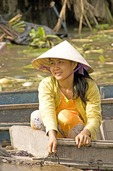 Vietnamese woman on boat at Phung Hiep floating market in Mekong River Delta near Can Tho