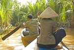 Vietnamese guides paddling backwaters of Mekong River Delta on canal tour near Ben Tre