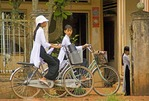 Vietnamese school girls in uniforms bicycling through countryside in the Mekong River Delta near Can Tho