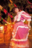 Guadalajara senorita in traditional Jalisco folk costume dancing at festivity