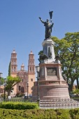 "Dolores Hidalgo's Parroquia de Nuestra Senora de los Dolores (Our Lady of the Sorrows parish church) behind statue of Father Miguel Hidalgo y Castilla in town plaza of Mexico's ""Cradle of Independence"""