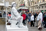 Mime on Las Ramblas in Barcelona sitting on toilet reading newspaper attracting attention of amused and curious pedestrians