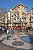 Las Ramblas in Barcelona with pedestrians on Joan Miro mosaic tile design in front of art deco building formerly an umbrella shop