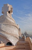 Antoni Gaudi sculpture (chimney) on roof of La Pedrera Museum in Barcelona with Sagrada Familia under construction in the distance