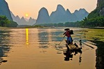 Li River cormorant fisherman on bamboo raft at Xingping (Yangshuo/Guilin area) at sunset