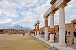 Ancient Roman city of Pompeii with Doric columns of the Eumachia Building facing the Forum with Temple of Jupiter and Mount Vesuvius at left