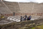 Ruin of Pompeii's small Greek theater or Odeon with students studying site
