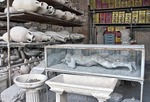 Ancient Roman city of Pompeii, Forum Granary area where relics unearthed include plaster cast of victim in a display case